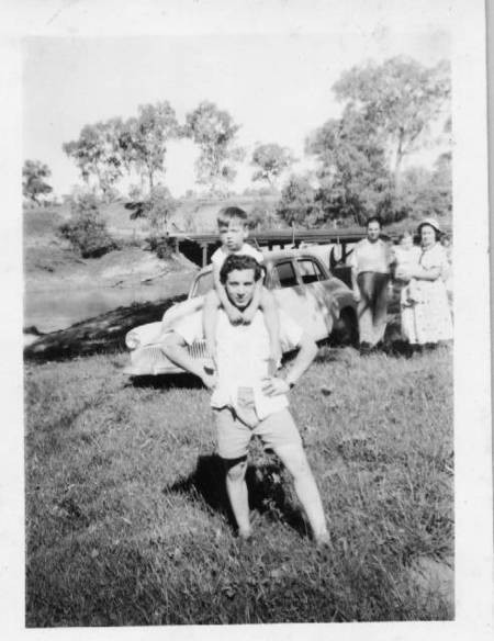 Manuel (Belo) Coroneos piggy backing an infant Chris Miller, on a Chinchilla, Queensland, picnic.
