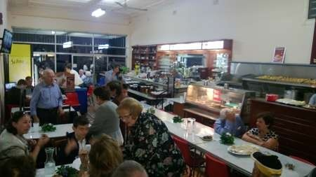 Another view from inside the Canberra Cafe of persons sitting down to eat and drink during the the afternoon  uncheon