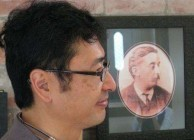 Bon Koizumi poses with a portrait of his great-grandfather, Lafcadio Hearn. (