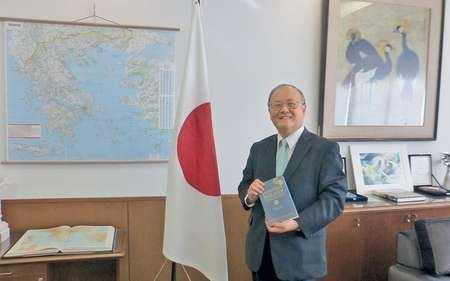 Ambassador of Japan to Greece Masuo Nishibayashi holding a copy of Lafcadio Hearn's Japanese Miscellany