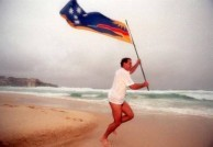 George C Poulos running across the sands of Bondi Beach with the official Bondi Beach Flag - his own design