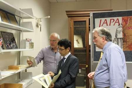 Takis Efstathiou, Bon Koizumi, and Leon Miller examining photographs in the Hearn collection at Tulane University