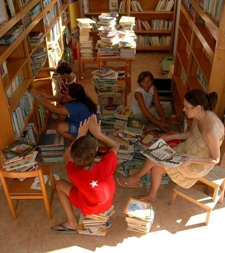 Children assisting volunteers to place books in the Childrens Library