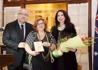 Maria Hill presented with an award by the Greek Ambassador Charalambos Dafaranos and his wife Eva