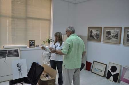 Takis Efstathiou and Theodora Georgaki, who is in charge of Art exhibits at the Cultural Centre examining new art work donated by Takis.