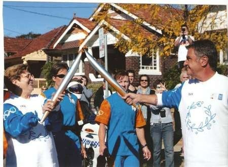 The late Rita Comino hands over the Olympic torch to Nick Politis